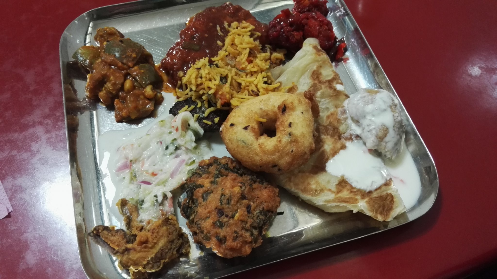 Various Indian vegetarian dishes on a silve plate