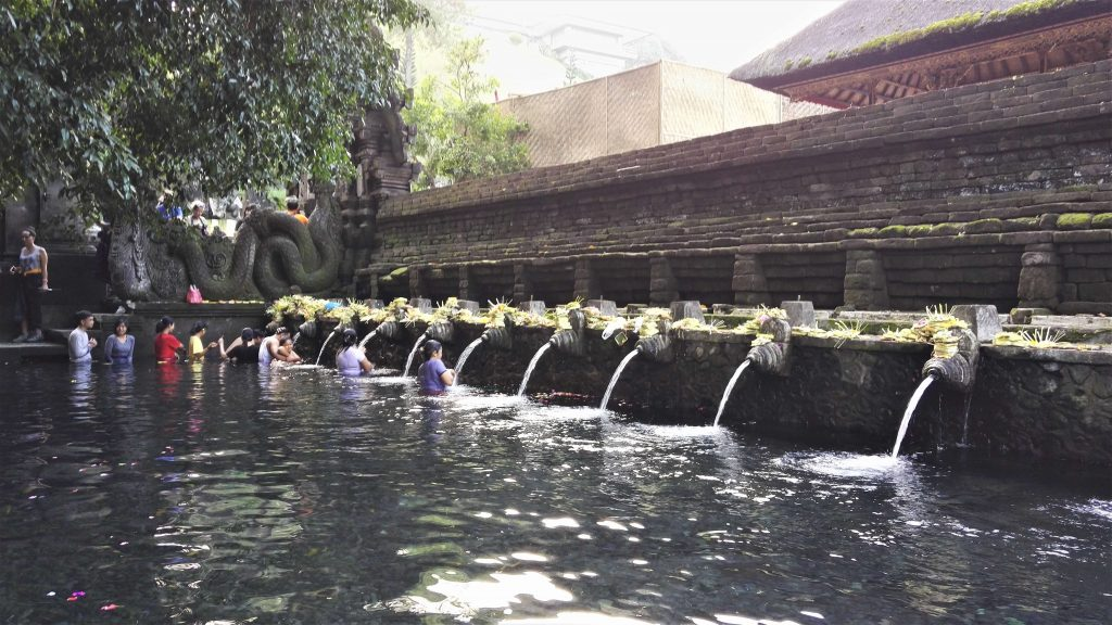 people in the pond splashing holy water on them at the Tirta Empul temple area