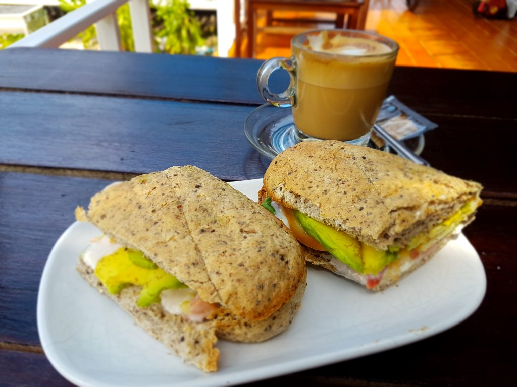 The delicious avocado sandwich and a cappuccino