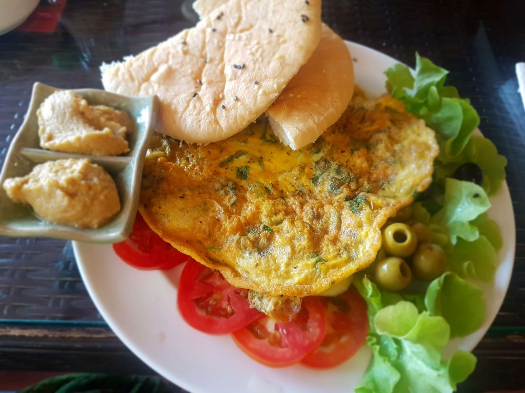 Omelet, hummus, flat bread, tomatoes and olives on a plate