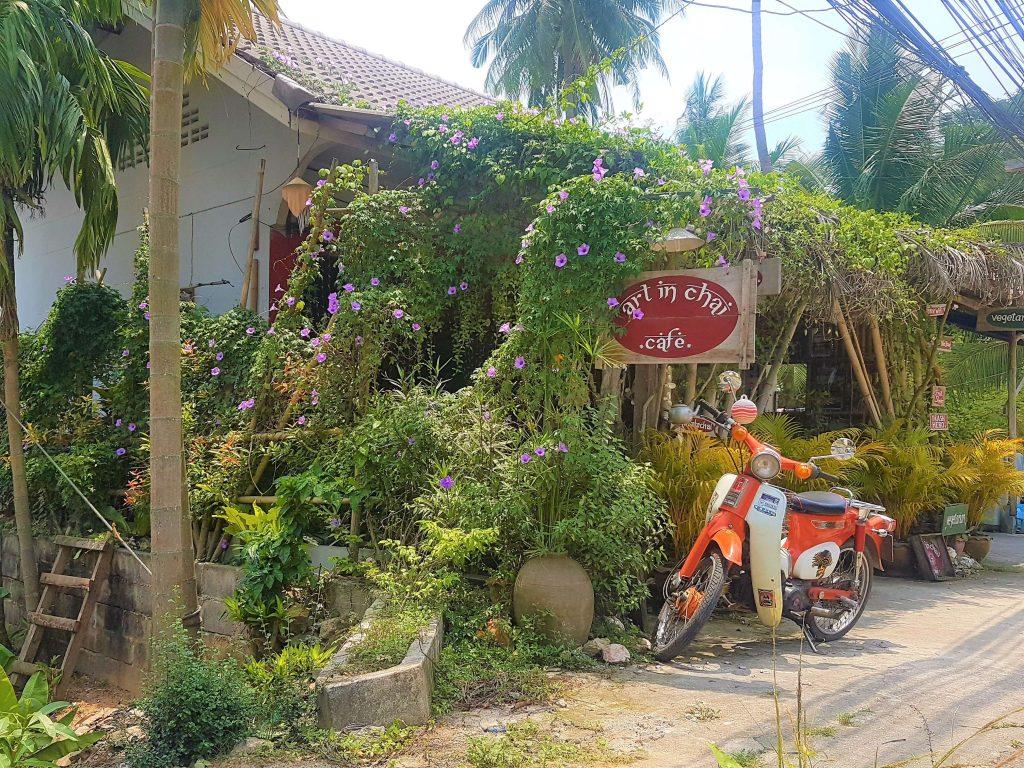 Art in Chai outside, covered in vegetation