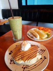 Pancake, green smoothie and a fruit salad