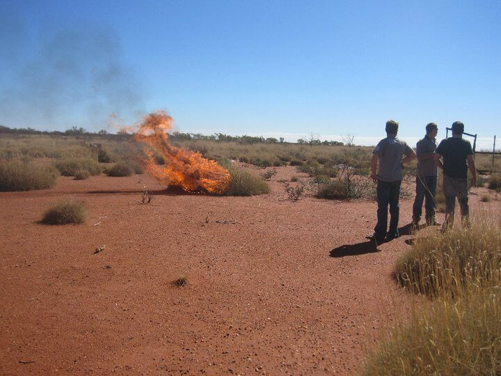 An arid desert view with a small fire