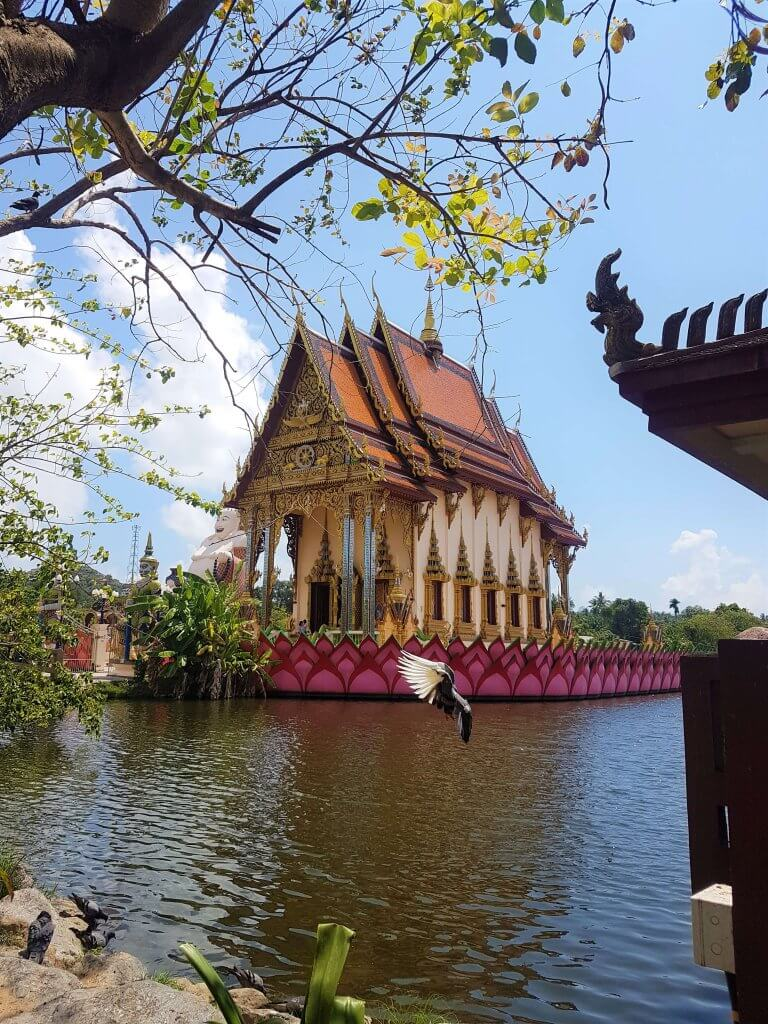 A beautiful Thai temple with orange roof erected on an island