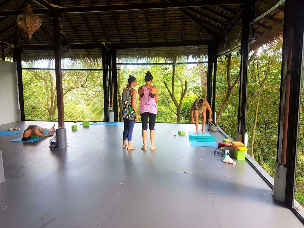 Students picking up their mats after a class in the Sunny Yoga jungle shala