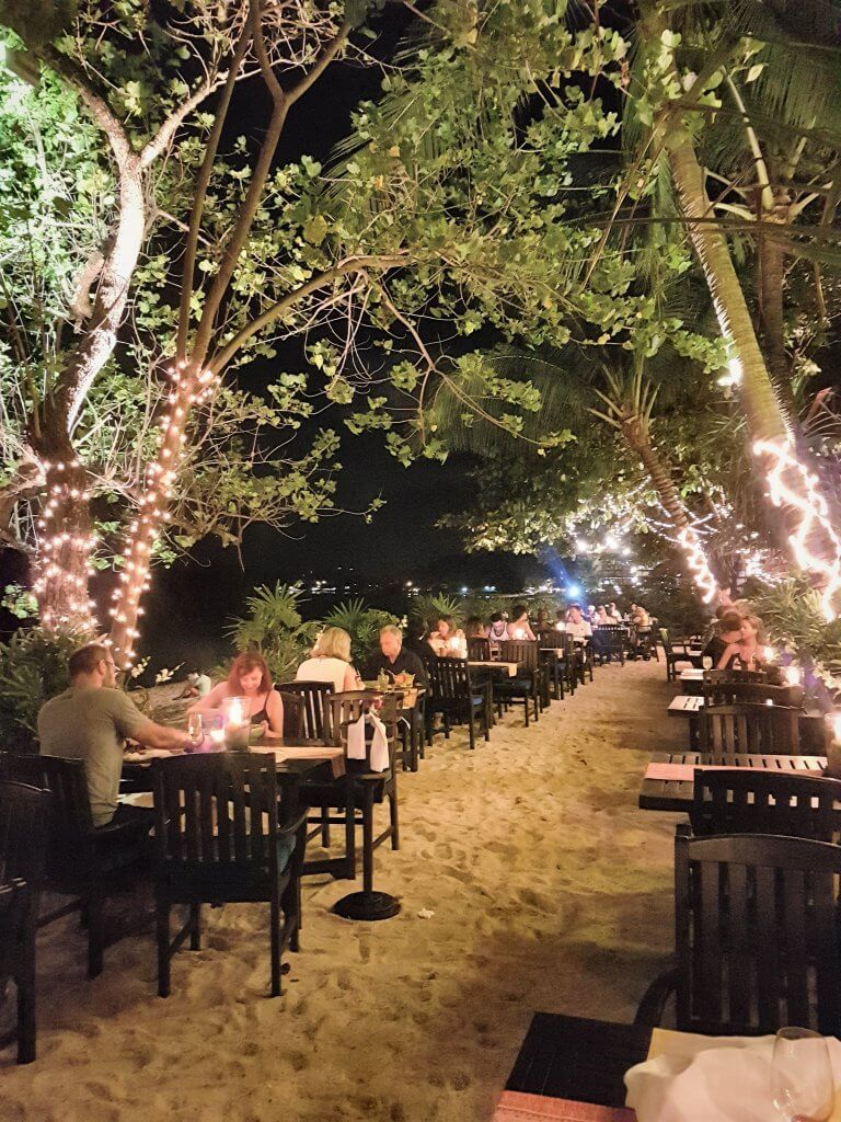 Tables on the beach, surrounded by trees which have light on