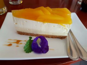 a piece of mango cheesecake