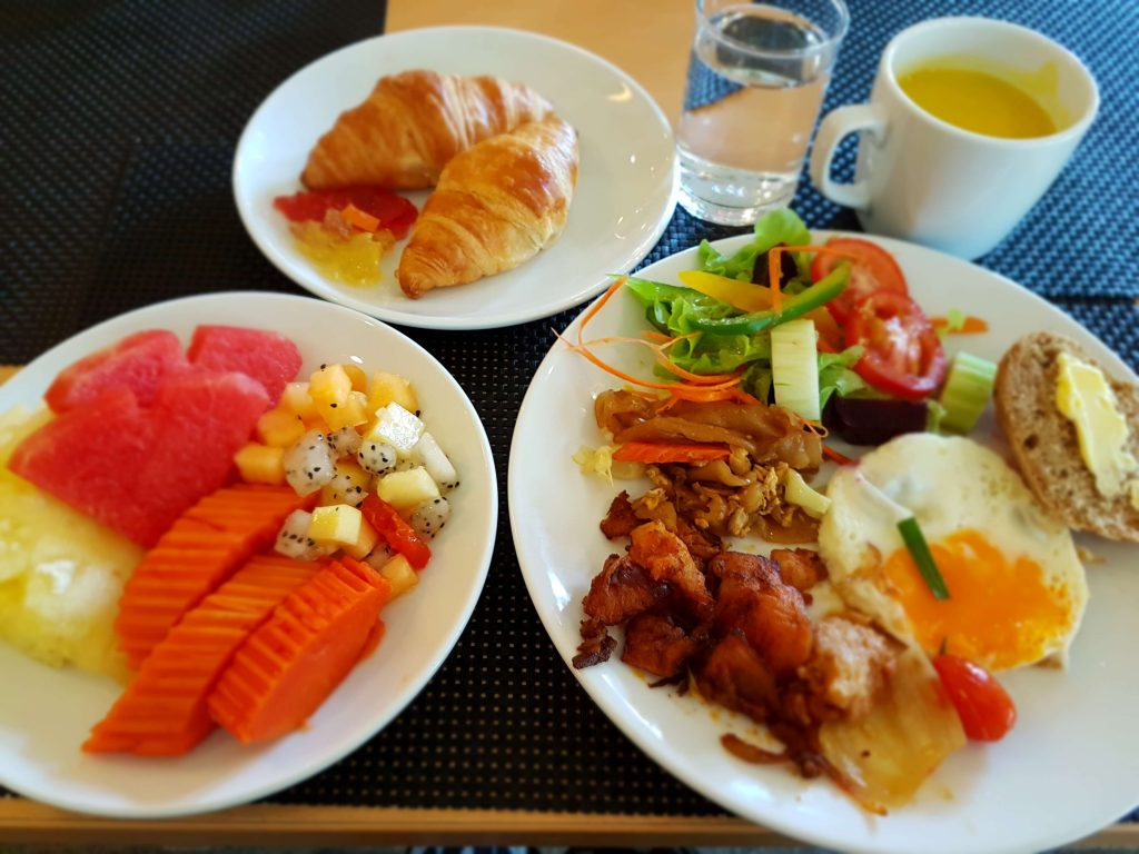 Fruits, croissants, and a selection of breakfast items on a plate