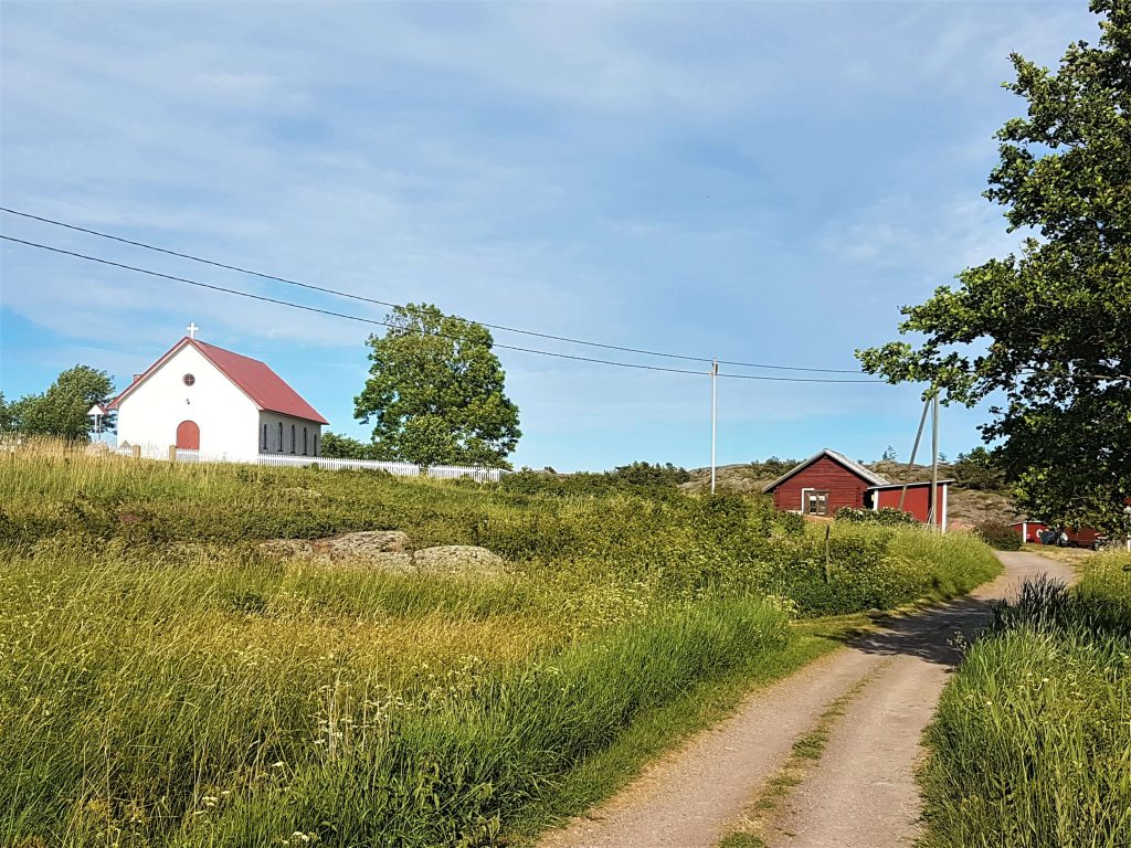 Field and a dirt road with a red barn and the church in the background