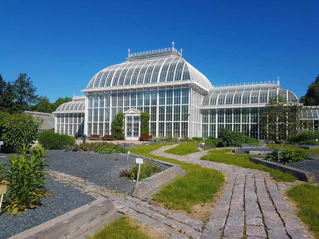 A huge greenhouse with white supporting structure and garden in the front yard