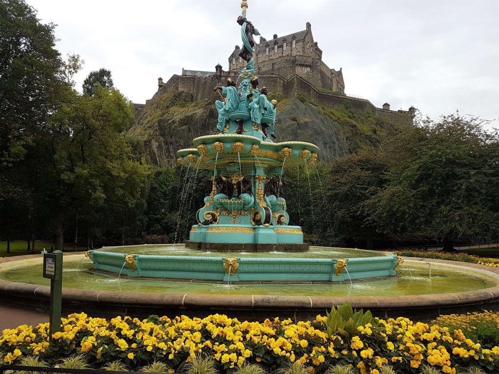 A fountain in the Princes Street Gardens with the Castle in the background