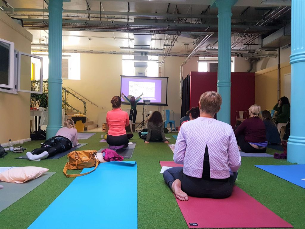 The spacious room where the yoga therapy course took place with yoga mats on the floor and people sitting on them