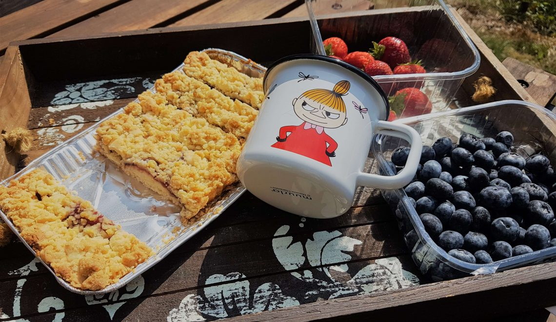 A pie, fresh blueberries And strawberries with a Mumin mug
