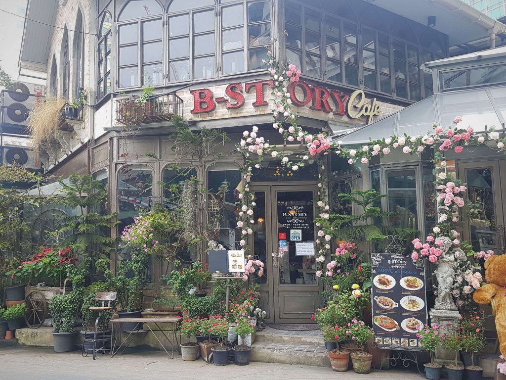 B-story cafe with flowers and decorations at the entrance
